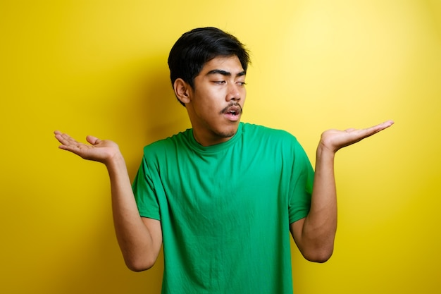 Portrait of male asian college student wearing green t-shirt shows choices between his empty hand palms, doubt concept against yellow background