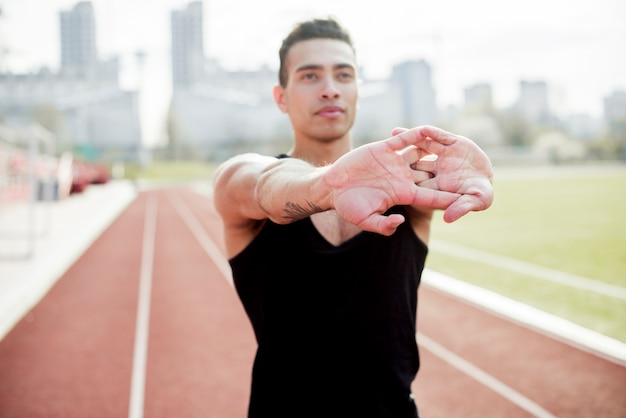Portrait of a male athlete stretching her hands before running on race track