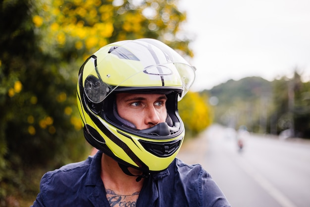 Portrait of male biker in yellow helmet on motorbike on side of busy road in thailand
