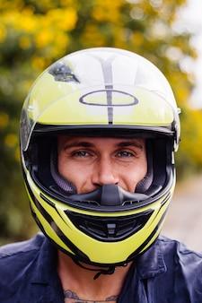 Portrait of male biker in yellow helmet on motorbike on side of busy road in thailand