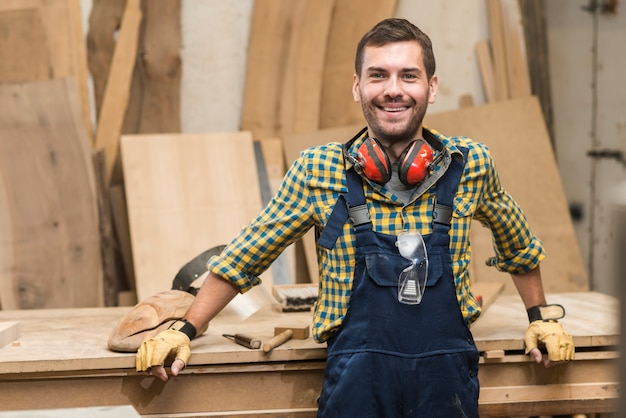 Portrait of a male carpenter standing in front of workbench