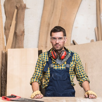 Portrait of a male carpenter wearing ear defender around his neck looking at camera