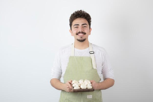 Ritratto di cuoco maschio che tiene piatto di funghi crudi su bianco