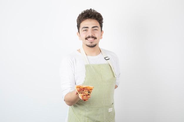 Ritratto di cuoco maschio che tiene una fetta di pizza su bianco