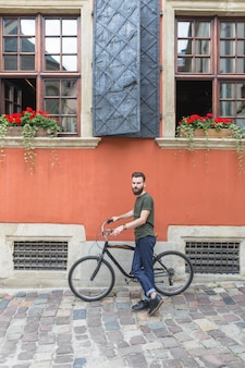 Portrait of a male cyclist with bicycle in front of building