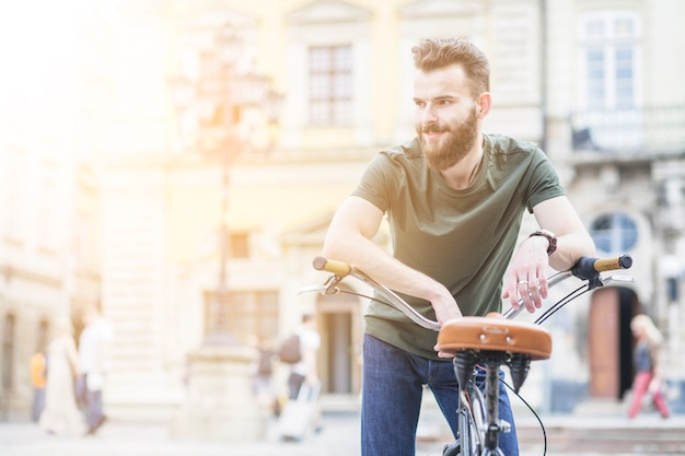 Portrait of a male cyclist with bicycle looking away