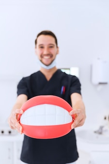 Portrait of male dentist showing teeth model at dental clinic