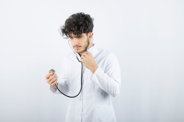 Portrait of a male doctor holding a stethoscope and listening .