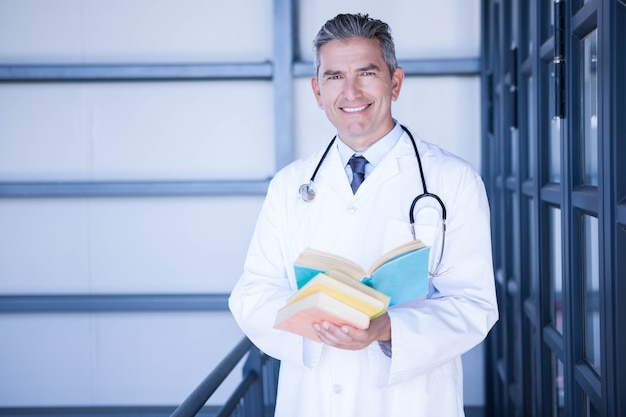 Portrait of male doctor standing with medical book in hospital
