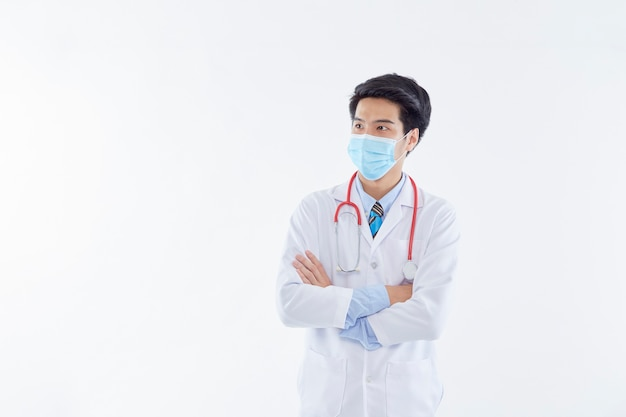 Portrait of a male doctor with arms crossed wearing a surgical mask.