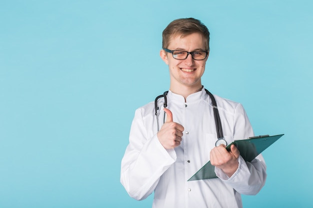 Portrait of male doctor writing on clipboard over a blue background showing thumbs up