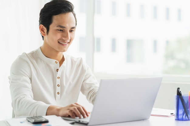 Portrait of male employee working on computer with happy expression