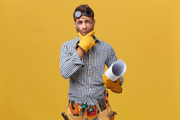 Portrait of male fettler wearing protective wear holding blueprint having thoughtful expression while thinking over his actions during work. repairman with kit of instruments isolated over wall