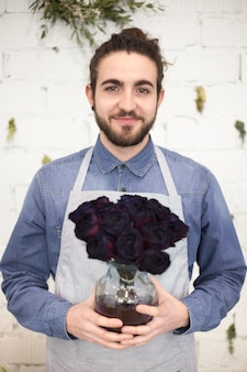 Portrait of a male florist holding rose flowers in the glass vase