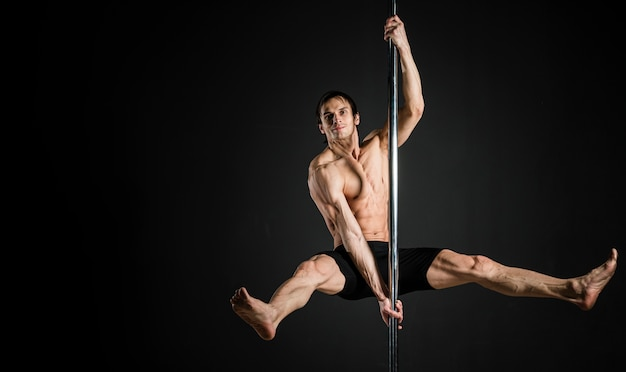 Portrait of male model performing a pole dance