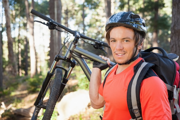 Portrait of male mountain biker carrying bicycle in the forest