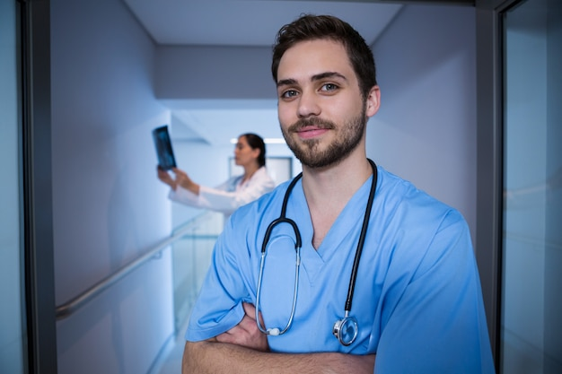 Portrait of male nurse standing with doctor in background