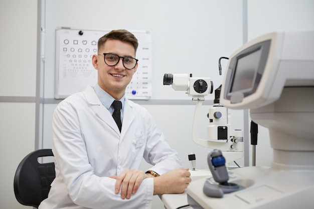 Portrait of male optometrist smiling at camera while posing at workplace by optic equipment