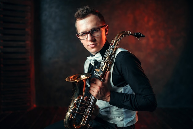 Portrait of male saxophonist with saxophone, jazz man with sax.