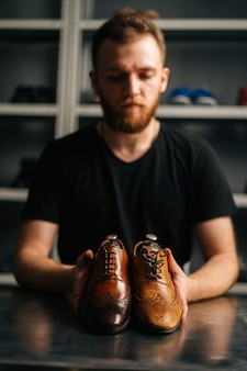 Portrait of male shoemaker holds old light brown leather shoe and repaired shiny shoes after restora...