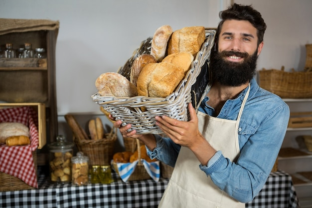 Portrait of male staff holding a basket of bread