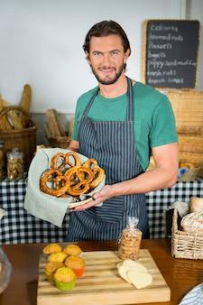 Portrait of male staff holding basket of pretzel at counter