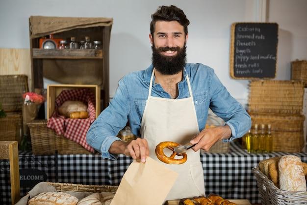 Portrait of male staff packing pretzel in paper bag