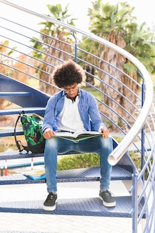 Portrait of a male student sitting on blue staircase reading the book at outdoors