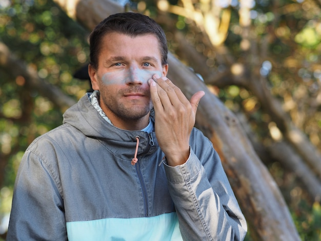 Portrait of a male surfer dressed in a hoodie applying colored sunscreen on his face. tropical environment.