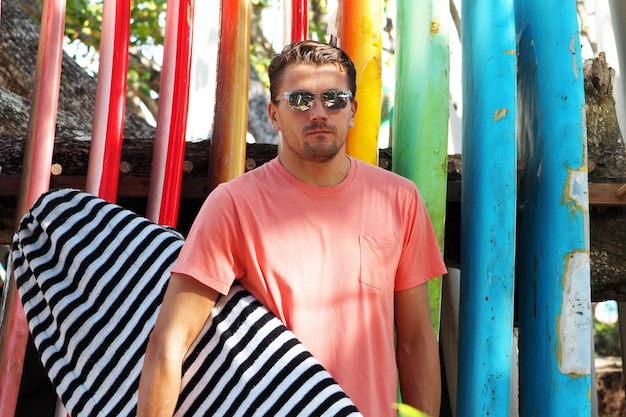 Portrait of a male surfer in a fashionable t-shirt holding a surfboard at the surfsport. background bright surfboards.