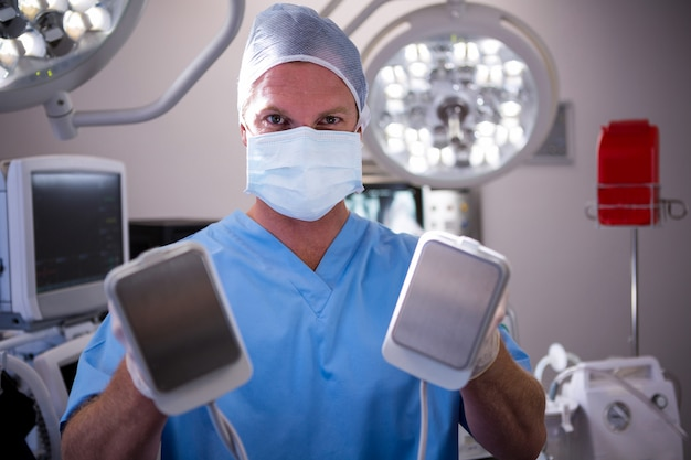 Portrait of male surgeon holding defibrillator