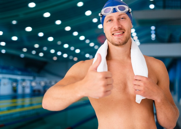 Portrait of male swimmer holding towel