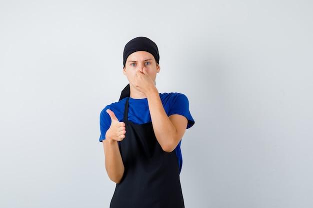 Ritratto di un cuoco adolescente maschio che pizzica il naso e offre stretta di mano in maglietta, grembiule e guarda dispiaciuto vista frontale
