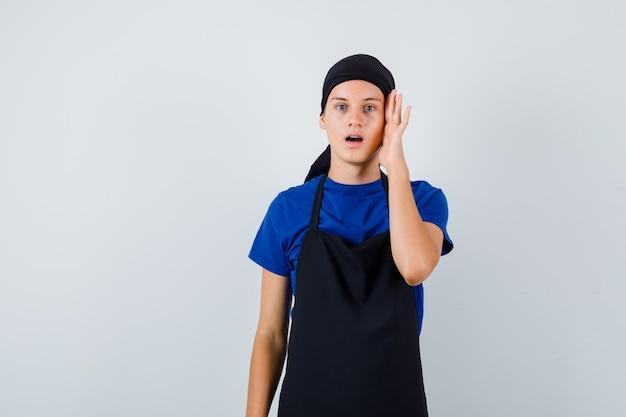 Ritratto di un cuoco adolescente maschio con la mano sulla testa, aprendo la bocca in maglietta, grembiule e guardando la vista frontale scioccata