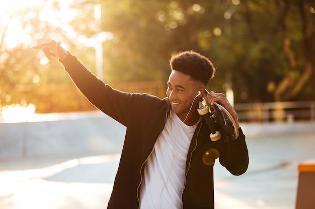 Portrait of a male teenager guy holding skateboard