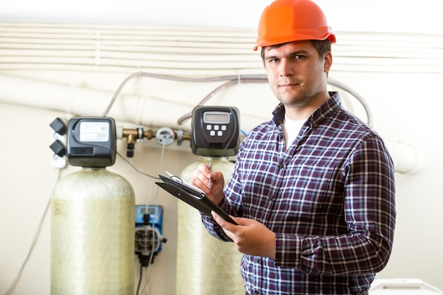 Portrait of male worker inspecting work of industrial equipment