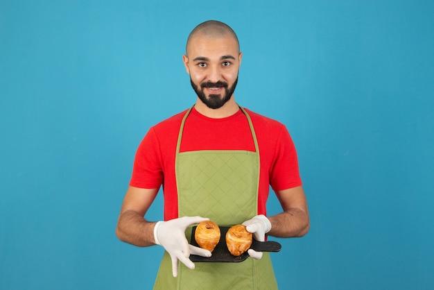 Ritratto di un uomo in grembiule e guanti che tengono pasticcini freschi.