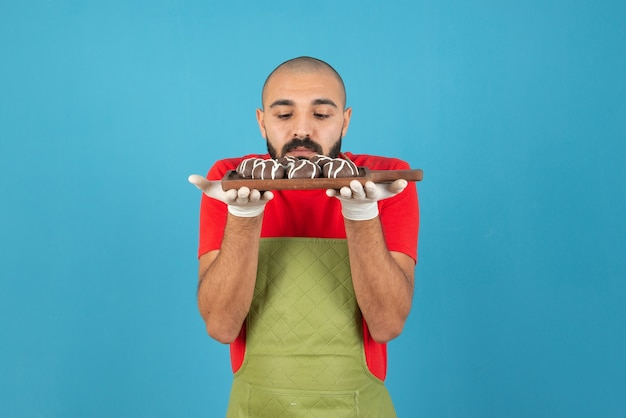 Portrait of a man in apron holding a wooden board with chocolate coated cookies .