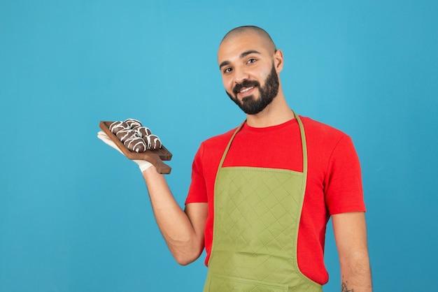 Ritratto di un uomo in grembiule che tiene una tavola di legno con biscotti ricoperti di cioccolato.