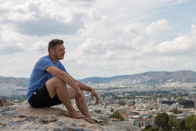 フィロパポスの丘から見たアテネのアクロポリスの肖像画の男。ギリシャの頂上から街を見下ろす