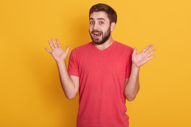 Portrait of man being surprised, handsome male spreading his hands up, posing isolated over yellow wall, attractive unshaven guy wearing red casual t shirt. the concept of human emotions.
