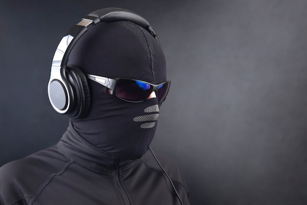 Portrait of a man in a black mask and sunglasses listening to music on headphones