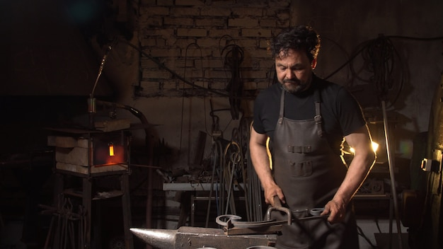 Portrait of a man of a blacksmith in the working atmosphere. brutal man looks and smiles.