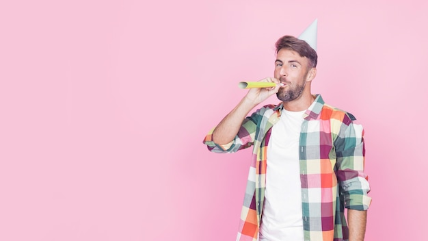 Portrait of a man blowing party horn on pink background