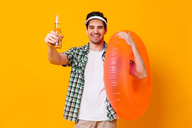 Portrait of man in cap, shirt and t-shirt holding bottle of beer and inflatable circle on isolated space.