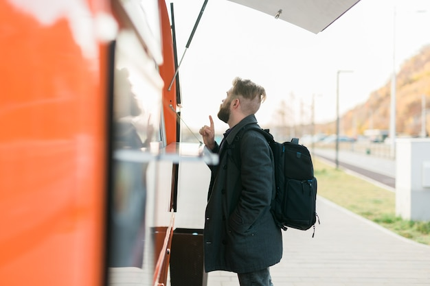 Portrait of man choosing fast food in food truck in the street meal food industry and streetfood