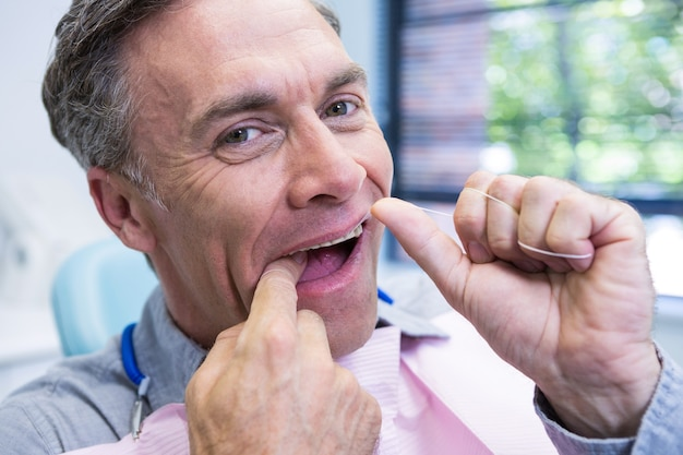 Portrait of man cleaning teeth with string