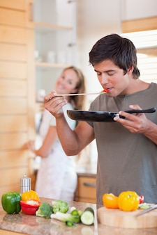 Portrait of a man cooking while his girlfriend is washing the di