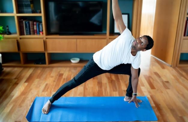 Ritratto di un uomo che fa esercizio rimanendo a casa. nuovo concetto di stile di vita normale. concetto di sport.