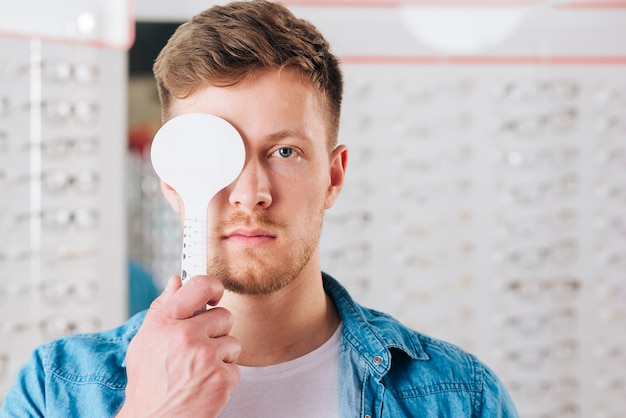 Portrait of man doing test of eye vision